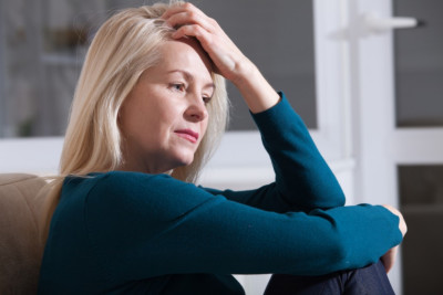 Sad depressed woman at home sitting on the couch