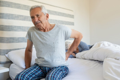 Senior men suffering from back pain at home while wife sleeping on bed