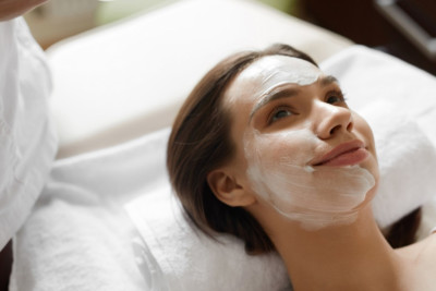 Smiling woman with white cosmetic mask on her face